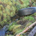 Large tyre dumped in water channel.